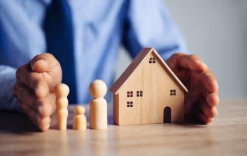 assurance habitation 2021 - homme protégeant une maquette de maison entre ses mains
