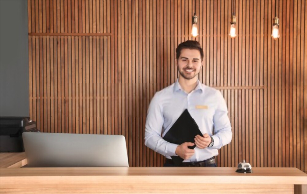 Jeune concierge d'entreprise homme qui est derrière un bureau