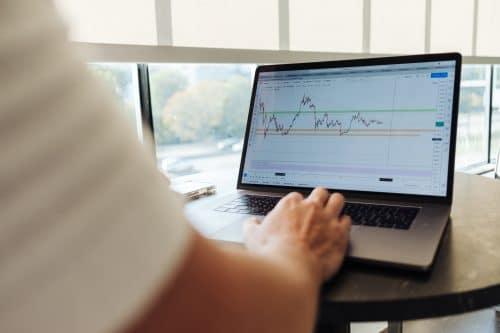 photo d'un homme devant son ordinateur sur un site de courtier en bourse pour illustrer l'article comment choisir son courtier en bourse