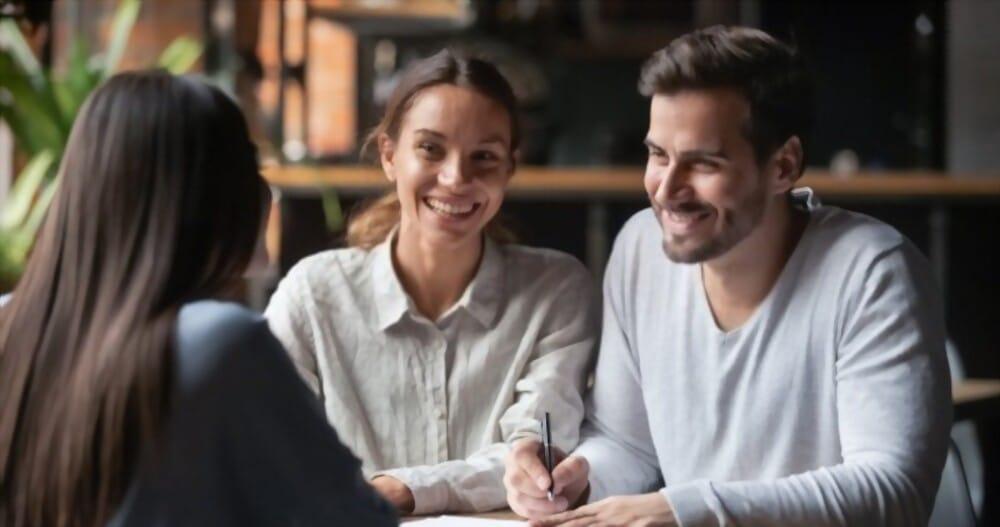 Joyeux jeune client couple prêt à signer un contrat de prêt bancaire avec un courtier immobilier