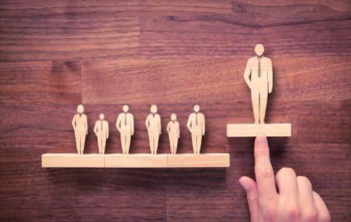 Représentation de personne en bois sur une planche plus foncée avec un personnage plus grand qui est le leader