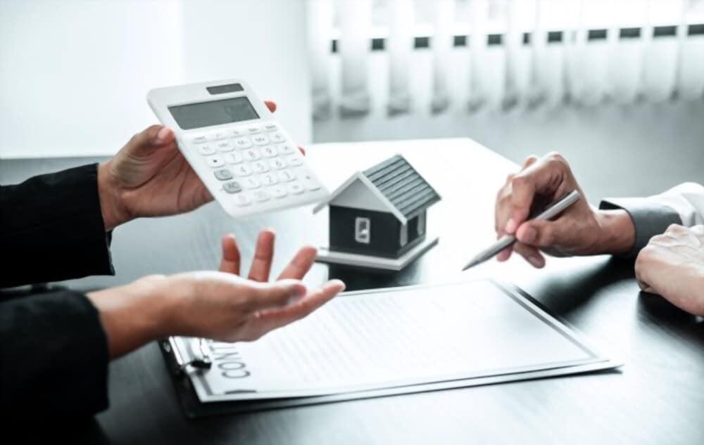 agent immobilier qui estime la valeur de l'appartement de son client autour de plans et d'une calculette