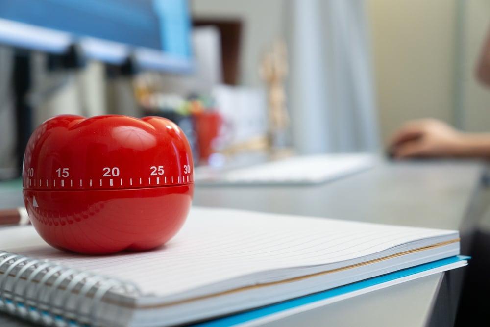 technique pomodoro - minuteur pomodoro en forme de tomate posé sur un bureau pour améliorer sa gestion du temps de travail