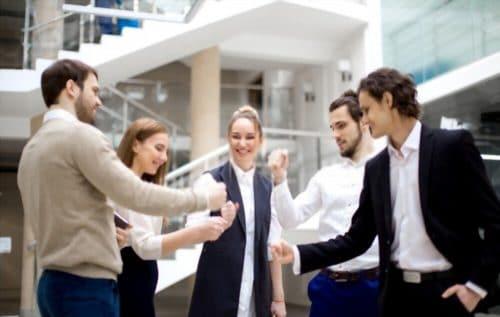 équipe de travail jouant à un jeu de pierre feuille papier ciseau dans le cadre d'un team building