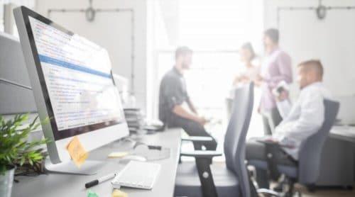 Employé d'une agence web discutant en arrière plan avec ordinateur en premier plan