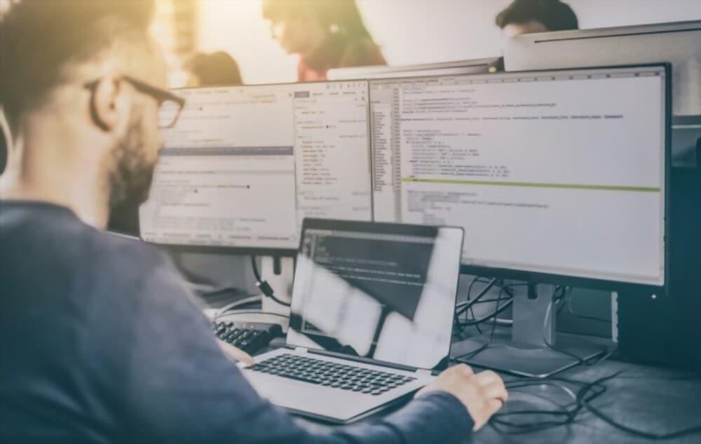 Développeur entrain de coder devant son ordinateur et deux écrans externes
